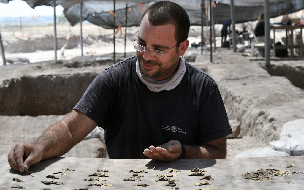 Shahar Krispin, Israel Antiquities Authority coin expert, counts the gold coins (Yoli Schwartz, Israel Antiquities Authority)